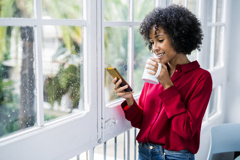 Smiling woman with cup of coffee and cell phone standing at the window at home - GIOF05543