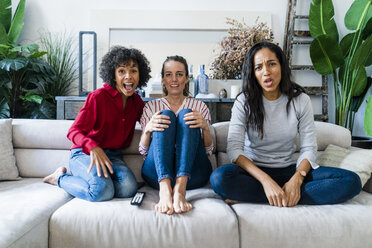 Three excited women on couch at home watching Tv - GIOF05546