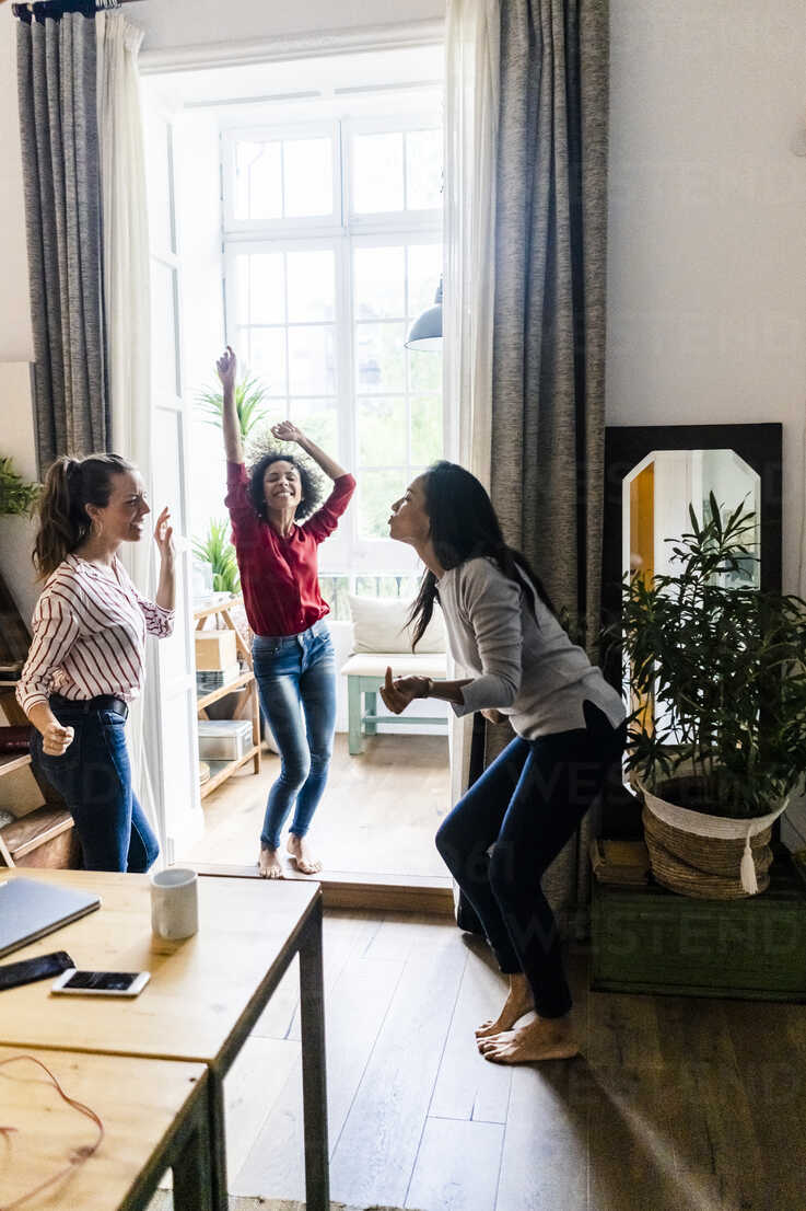 Three women at home having a party and dancing - GIOF05549 - Giorgio Fochesato/Westend61