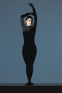 Portrait of woman dressed in black with flare on her face doing stretching exercise - VGF00190