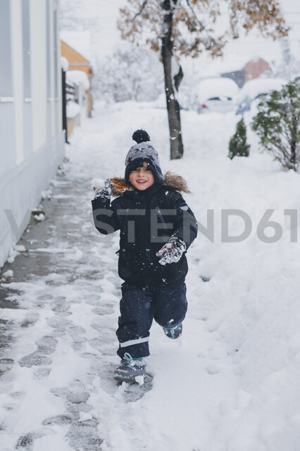 Portrait of smiling toddler throwing snowball - MOMF00584