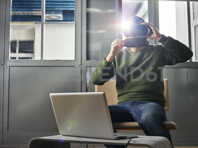 People Lifestyle, (mit Release) Mann 30-35 Jahre sitzt mit VR Brille vor Laptop, Wattens, Tirol, Austria - CVF01119