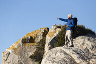Spain, Andalusia, Tarifa, man on a hiking trip standing on rock pointing his finger - KBF00414