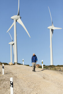 Spain, Andalusia, Tarifa, man on a hiking trip walking on dirt road surrounded by wind turbines - KBF00417