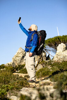 Spain, Andalusia, Tarifa, man on a hiking trip in the mountains taking a selfie - KBF00420