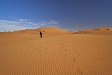 Morocco, back view of man with backpack standing on desert dune - EPF00544