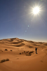 Morocco, Sahara, man with backpack standing on desert dune looking at view - EPF00550