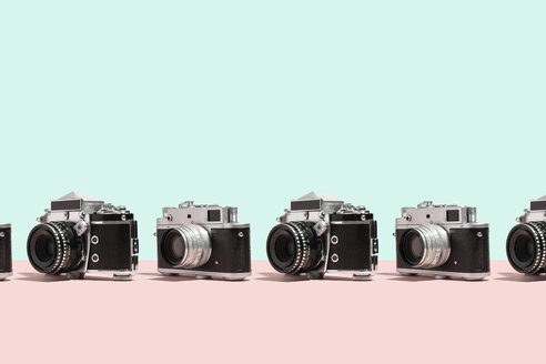 Photo cameras organized in a row over colorful background - DRBF00129