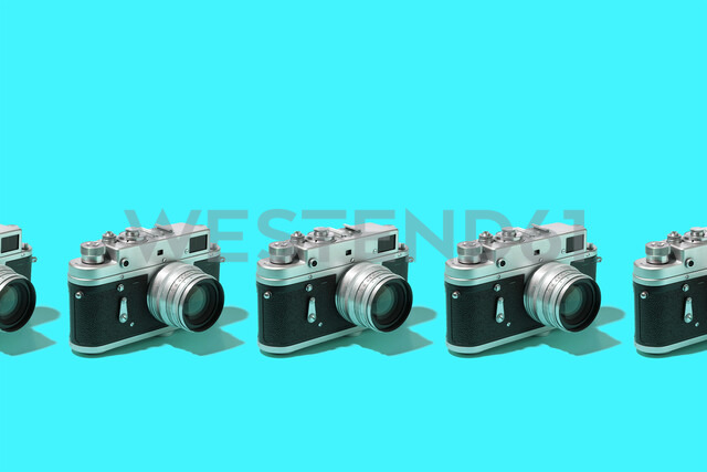 Photo cameras organized in a row over blue background - DRBF00132