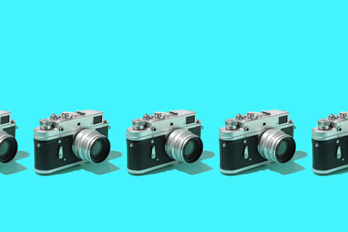 Classic photo cameras organized in a row over blue background - DRBF00132
