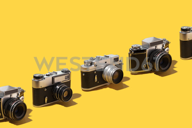 Photo cameras organized in a row over yellow background - DRBF00135