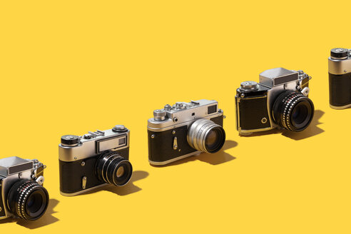 Classic photo cameras organized in a row over yelow background - DRBF00135