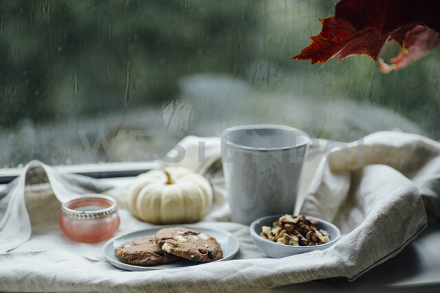 Cup of coffee, cookies and autumnal decoration on window sill - JESF00196