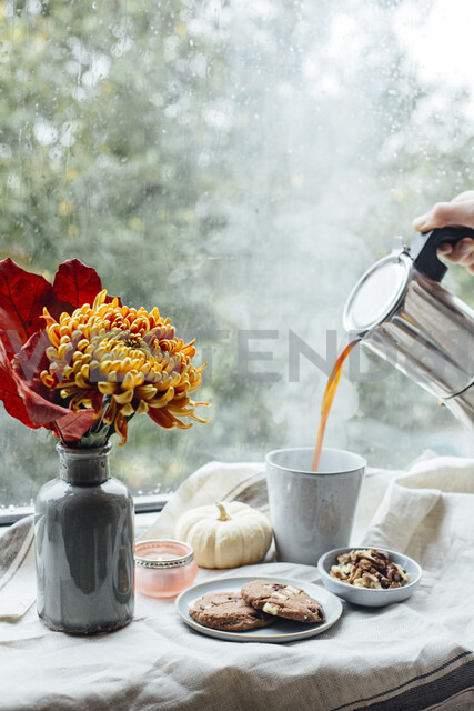 Woman's hand pouring hot coffee into a mug on rainy day - JESF00199