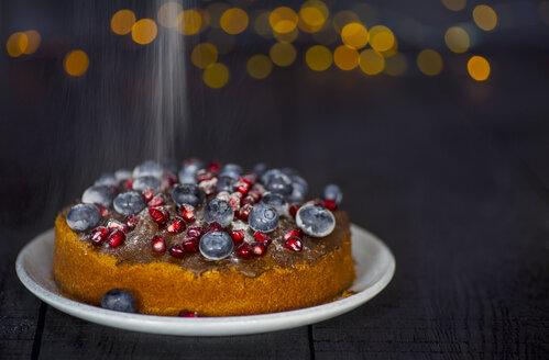 veganer Kuchen mit Heidelbeeren und Granatapfelkernen, außerdem Schokoladenüberzug; Puderzucker wird darüber gestreut - JESF00205