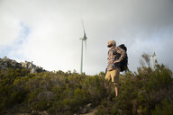Spain, Andalusia, Tarifa, man on a hiking trip with wind turbine in background - KBF00434