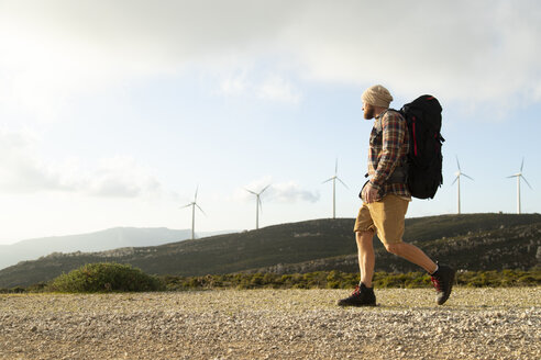 Spain, Andalusia, Tarifa, man on a hiking trip walking on dirt road with wind turbines in background - KBF00440