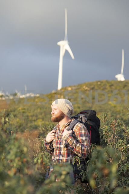 Spain, Andalusia, Tarifa, smiling man on a hiking trip with wind turbines in background - KBF00449