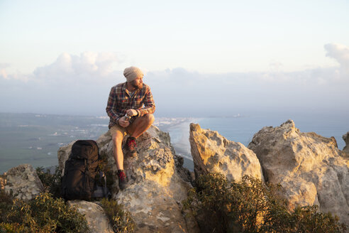 Spain, Andalusia, Tarifa, man on a hiking trip at the coast sitting on rock - KBF00452