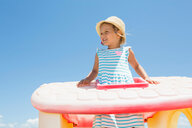 Girl in sun hat looking out from plastic roof on beach,  Castellammare del Golfo, Sicily, Italy - CUF47895
