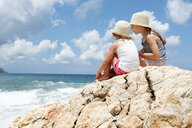 Two girls looking out at sea from rock, Scopello, Sicily, Italy - CUF47901