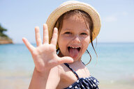 Girl in sunhat sticking out her tongue, portrait, Scopello, Sicily, Italy - CUF47904