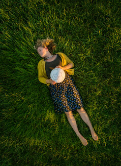 Teenage girl lying on grass with eyes closed holding soccer ball, overhead view - CUF47916