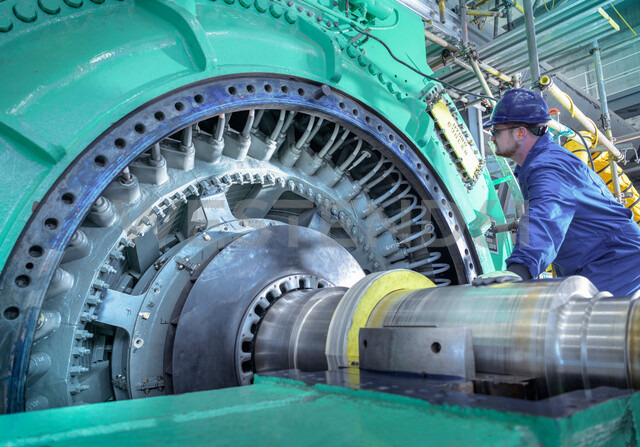 Engineer inspecting generator in nuclear power station during outage - CUF47952