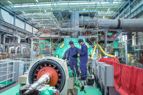 Engineers inspecting gears at generator end in nuclear power station during outage - CUF47955