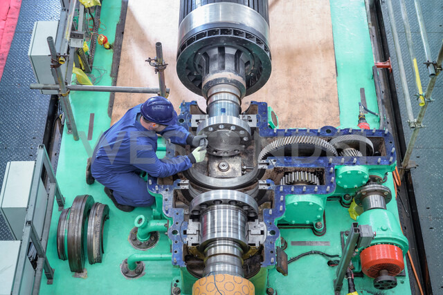 Overhead view of engineer inspecting gears on generator in turbine hall of nuclear power station during outage - CUF47958