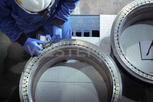 Overhead view of engineer measuring oil seals in nuclear power station during outage - CUF47961
