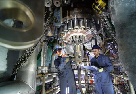 Engineers working in confined space under turbine during outage in nuclear power station - CUF47964