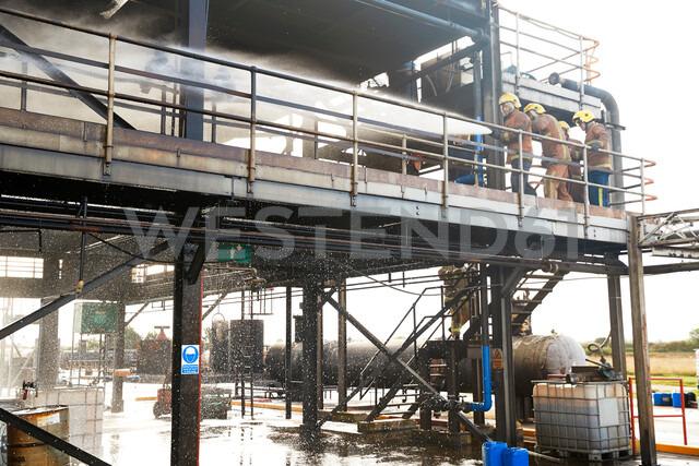 Firemen training, on training facility building spraying water - CUF47976