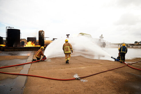 Firemen training, spraying water onto fire at training facility - CUF47979