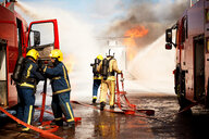 Firemen training, team of firemen extinguishing mock helicopter fire at training facility - CUF47982