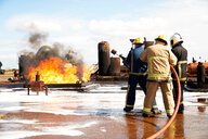 Firemen training, firemen preparing to put out oil storage tank fire at training facility - CUF47985