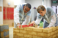 Male higher education students building brick wall in college workshop - CUF48006