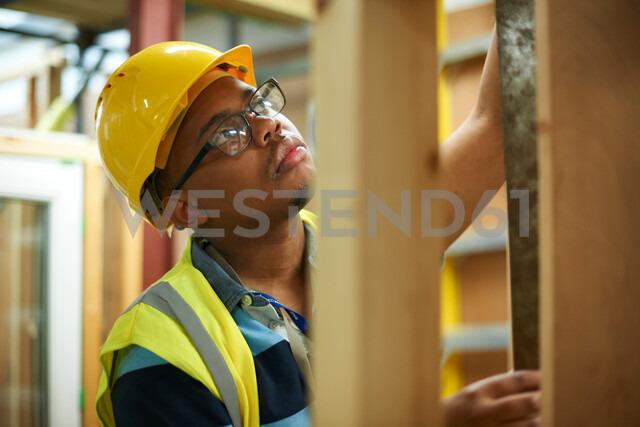 Male higher education student building wooden framework in college workshop - CUF48009