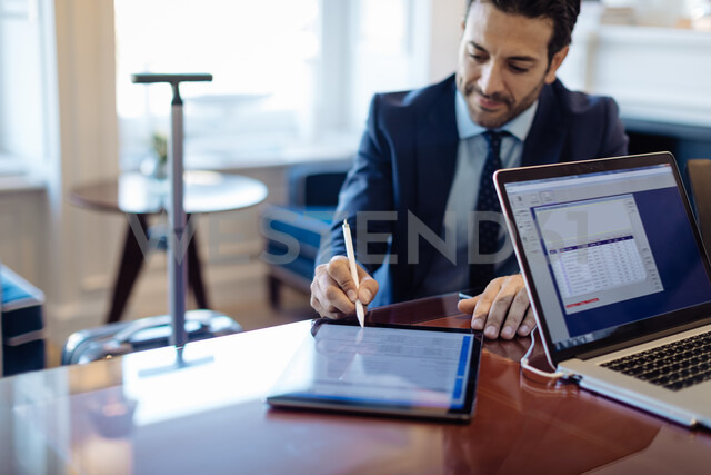 Businessman writing on digital tablet in office - CUF48054