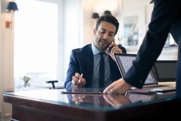 Businessman using smartphone in office - CUF48057
