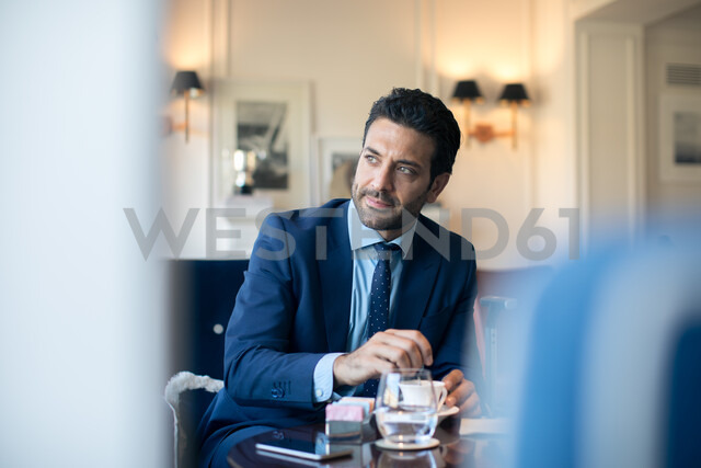 Businessman having coffee in office - CUF48060
