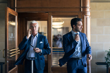 Businessman using smartphone and leaving office with colleague - CUF48066
