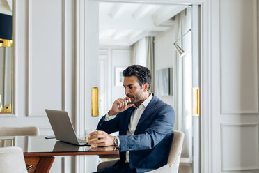 Businessman using laptop in suite - CUF48072