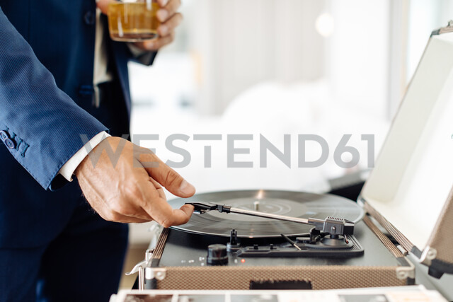 Businessman with iced drink, playing turntable in suite - CUF48081