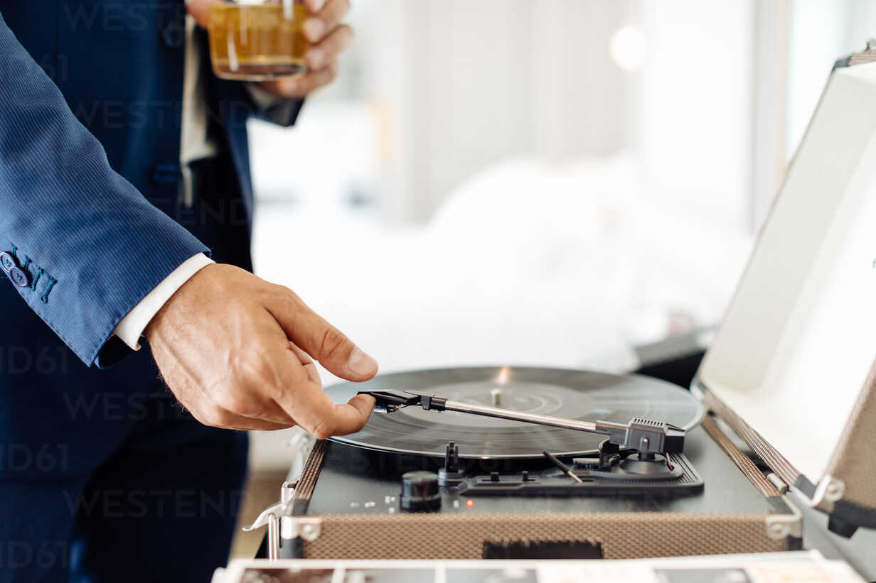 Businessman with iced drink, playing turntable in suite - CUF48081 - Sofie Delauw/Westend61