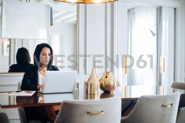 Businesswoman using laptop in suite - CUF48084