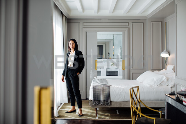 Businesswoman beside window in suite - CUF48087
