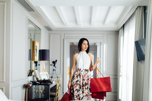 Fashionable woman with shopping bags in suite - CUF48093