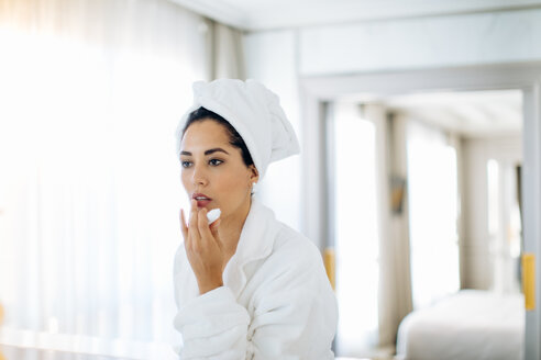 Woman applying lip balm in suite - CUF48096