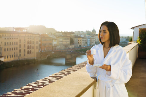 Woman having coffee on hotel balcony, Florence, Toscana, Italy - CUF48099